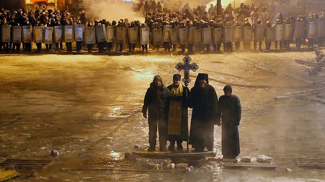 Courageously vulnerable in this place and time, Orthodox priests pray as they stand between protesters and the police in Kiev early Friday. Sergei Grits/Associated Press | Flickr - Photo S...
