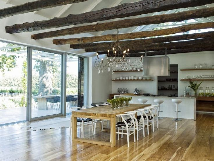 white cathedral ceiling with reclaimed wooden beams and open shelving on white wall and pantry with three large glass lime jars and curved back dining chairs with faux cowhide seats and sliding glass doors to patio