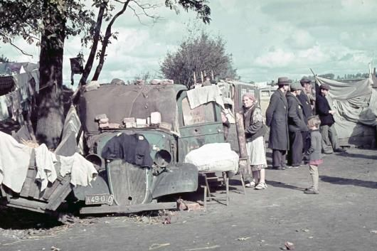 Kunto, Poland, circa 1940 - Displaced Jews stand outside a car that's been converted into a shelter in the Kunto Ghetto