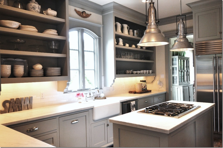 Sally Wheat kitchen--stovetop on the island + drawer hardware + farmhouse sink + industrial light fixtures + granite counteres + shaker style doors + gray paint + white subway tile