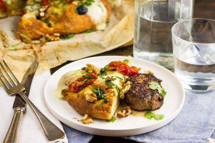 Recept voor huisgemaakte focaccia voor 4 personen. Met zout, water, olijfolie, peper, bakpapier, rundertartaar, broodmix, mozzarella, zongedroogde tomaten, olijf, rozemarijn, slamelange en balsamico azijn