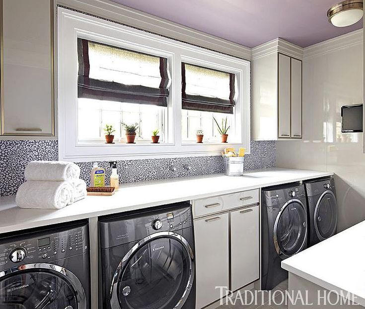 Amazing laundry room features a purple ceiling over two sets of washers and dryers tucked below a long white quartz countertop flanking white cabinets with metal trim place below walls dressed in Farrow and Ball Ocelet Wallpaper framing windows dressed in gray roman shades with purple trim.