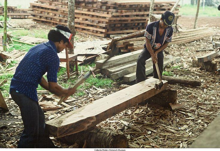 Arbeiders bewerken hout in een werkplaats voor botenbouw