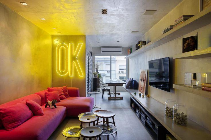Apartamento em cimento queimado do piso ao teto, de cor neutra com toques de cores vibrantes no sofá e letreiro luminoso. - Apartamento MM / Studio RO+CA