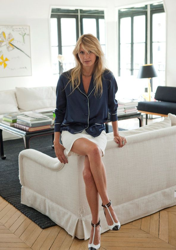 Perched on a linen sofa she designed, Lavoine wears a Salvatore Ferragamo top, a denim skirt by Stella McCartney, Manolo Blahnik strappy heels and Stone jewelry by her sister, Marie Poniatowski.