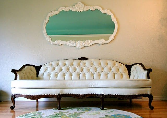 love the idea of using white vinyl to reupholster an antique sofa. it looks so crisp and clean against the dark wood.