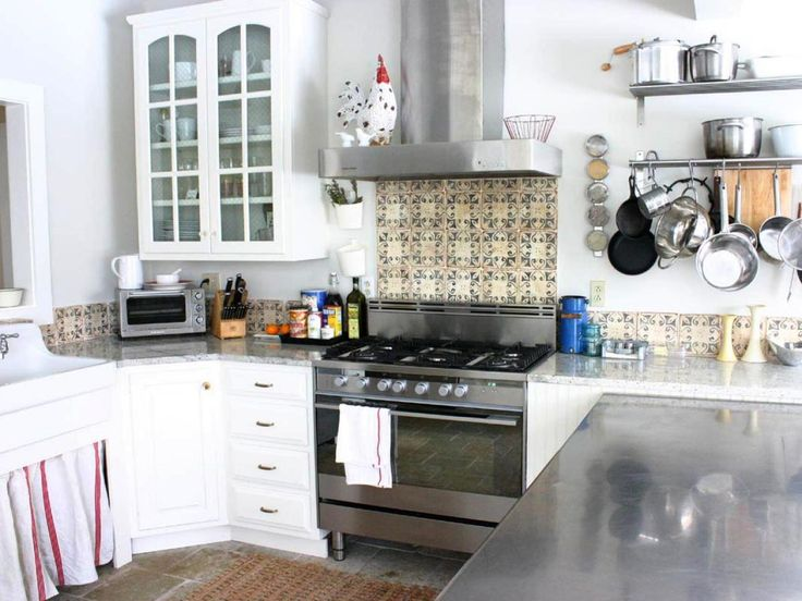 A country-patterned tile backsplash gives this kitchen designed by Rebekah Zaveloff a rustic look.