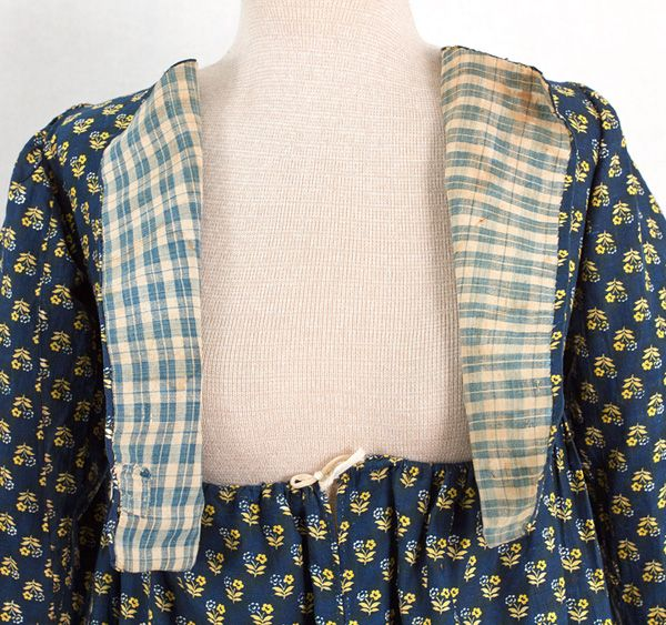"""#1866         $2,500  American rural indigo cotton print dress, c.1795-1810  This transitional-style dress, hard to date accurately, may have been remade from an earlier garment. The open front bodice without bust darts is cut in the 18th century manner. The blue-ivory plaid bodice lining is identical to linings of other 18th century New England dresses.  The bust measures 31"""" with the fronts just touching. The waist is adjustable by drawstring. The length is 49"""" from shoulder to hem."""