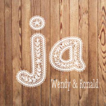 Hippe trouwkaart met warm houten achtergrond. Daarop in kanten letters het woord 'ja'. Daaronder plaats voor jullie namen.