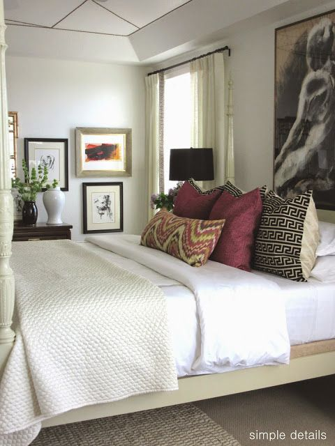 layered bed, mixed pattern pillows in large and small prints + solid, large art above bed