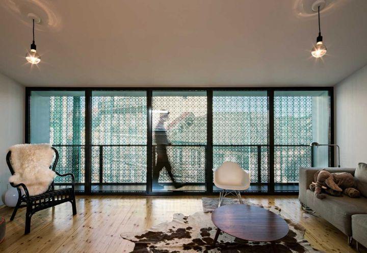 5 livelli per l'abitazione realizzata da Camarim Arquitectos nel cuore di Lisbona. Living con pavimento in parquet, divano modulare Muji, poltroncina Ikea con calda pelliccia di agnello e sedia a dondolo Eames RAR di Vitra