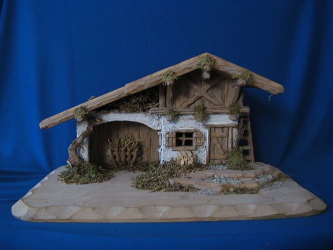 """A very special, hand-made, hand-carved nativity crib from Bavaria.  On a wooden platform (about 3/8"""" thick, 9-1/2"""" deep and 19"""" long), the building stands 8-1/4"""" tall. The architectural detail is charming--hay crib on the back wall, ladder on the right, woodpile, two windows, etc. Each one is unique!  Available at www.mygrowingtraditions.com"""