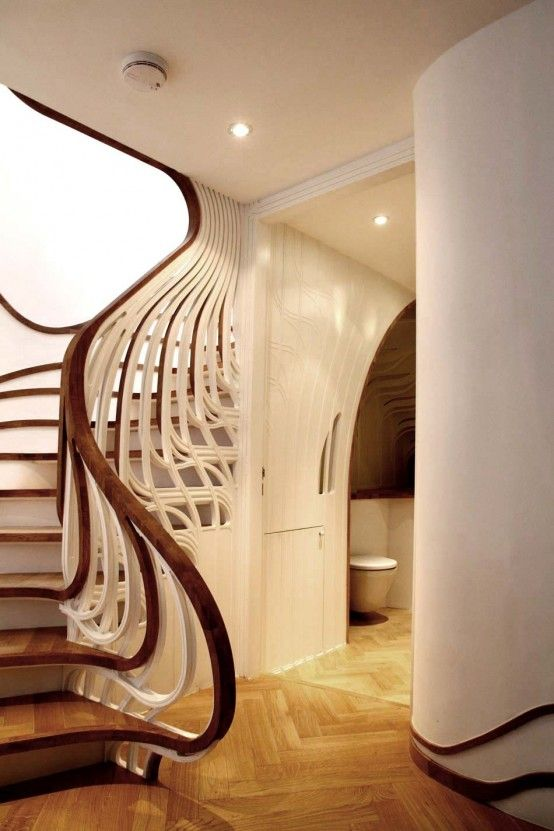 Love how the hard angles in the floor balance out the incredible curves in the staircase.