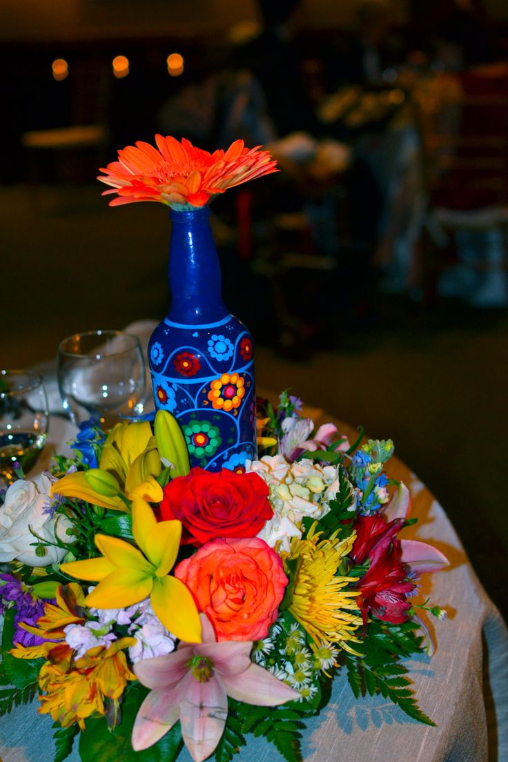 Centros de mesa con flores de colores y botellas pintadas a mano de Xochimilco