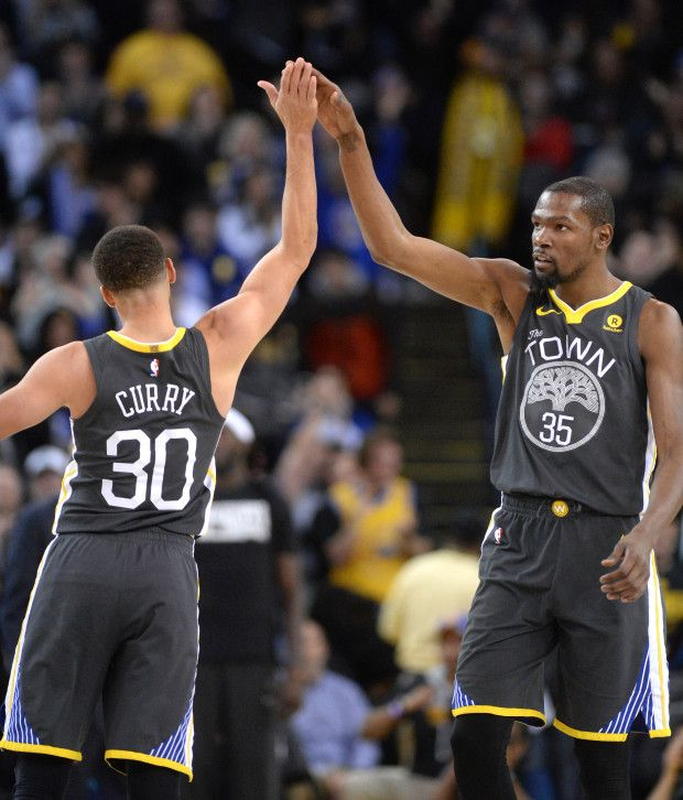 Golden State Warriors' Stephen Curry (30) celebrates with teammate Kevin Durant (35) after Curry made a three-point basket in the fourth period of their NBA game against the Los Angeles Clippers at Oracle Arena in Oakland, Calif., on Thursday, Feb. 22, 2018. (Doug Duran/Bay Area News Group)