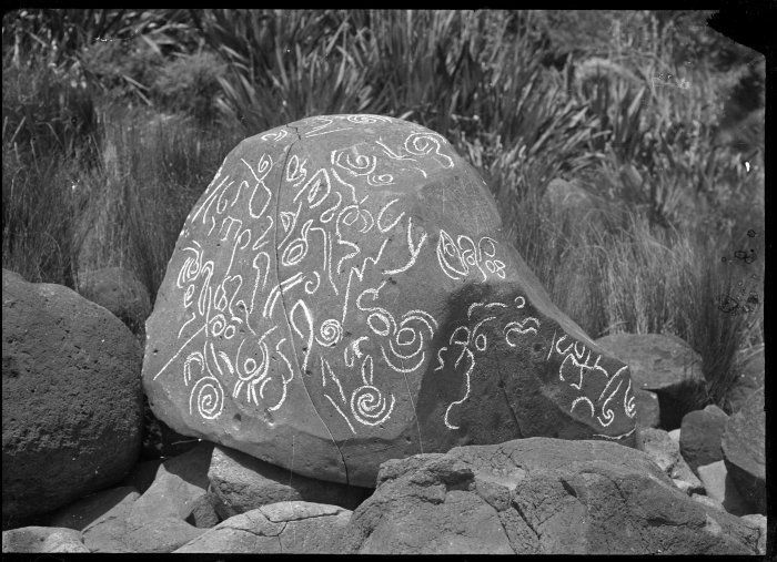 """Rock with Maori markings, at Raglan, [ca 1920] Reference Number: APG-0961-1/2-F Petroglyphs on an isolated rock near Raglan, photographed by Albert Percy Godber, circa 1920. For further information see """"Maori rock art"""" by Michael M Trotter, 1981. Known as Tattoo Rocks."""