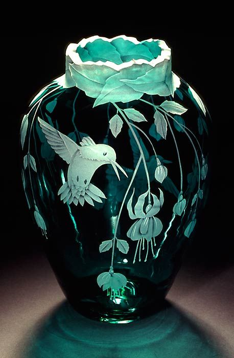 The vase is etched with many stems of these delightful flowers hanging down all the way around the piece. The lip of the vase continues the theme. The humming birds are wonderful - love the soft aqua color against the dark background...