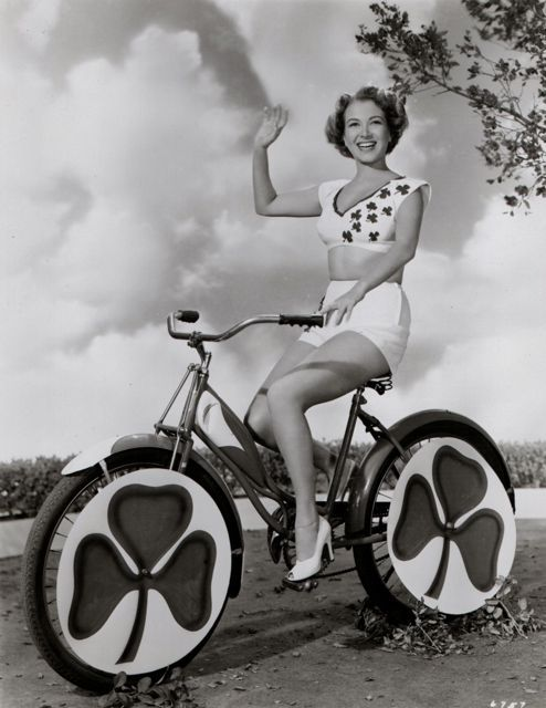 "Monica Lewis rides a ""be-shamrocked"" bike.A free-wheeling Colleen: MGM's modern Lady Godiva, Monica Lewis, won't be a-riding a white steed, but a be-shamrocked bike, in the St. Patrick's Day parade. Monica will make her screen debut with Red Skelton in MGM's ""Excuse My Dust."""