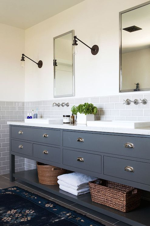 A pair of nickel framed medicine cabinets, flanked by Schoolhouse Electric Sconces, stand over a dark gray dual sink vanity with drawers adorned with cup pulls over a lower shelf lined with woven baskets and fresh white towels. The gray sink console is topped with a pair of shallow vessel sinks set atop a white marble counter with wall mount faucets above mounted on a gray subway tiled half wall backsplash.