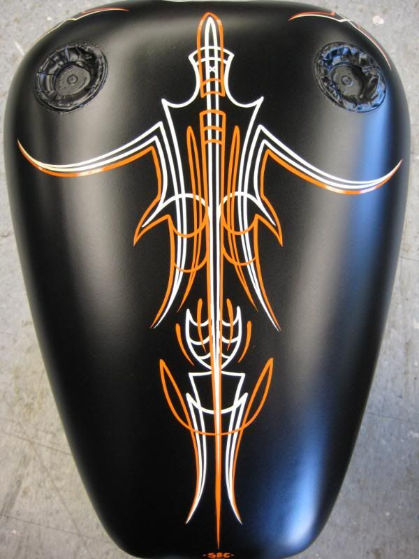 Pinstripe orange and white on a black motorcycle tank
