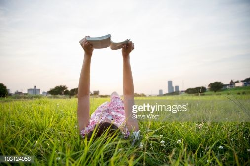 Stock Photo : Woman laying in grass reading a book