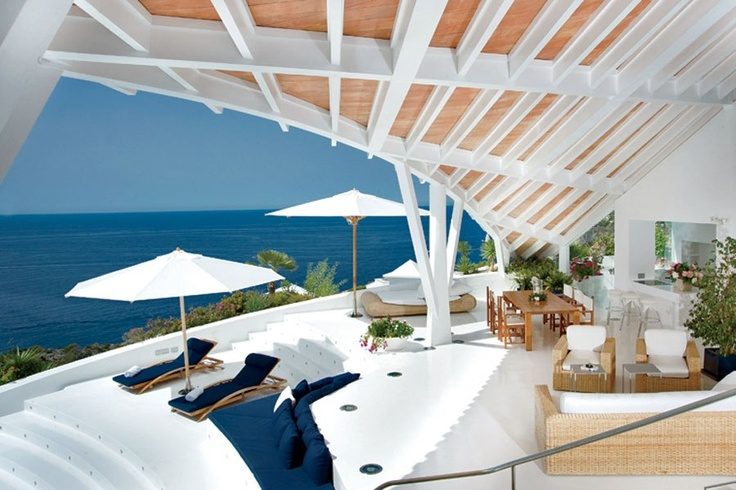 Majorca, Spain. Clean lines and glossy white surfaces predominate in this futuristic two-story villa, built in 2002 by local architect Alberto Rubio. Constructed on a cliff overlooking the fishing village of Port D'Andratx, the dramatic house is a seemingly endless maze of sundecks and airy open living spaces, all of which afford unrivaled vistas of the Mediterranean Sea.
