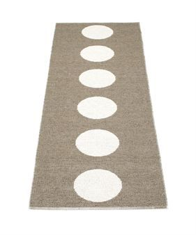 Vera is a jacquard woven plastic rug with a pattern of big dots in a straight line. The rug is two colored and is woven together with a vanilla colored plastic band.