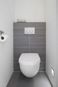 Modern ingerichte toiletruimte met zwevend toilet en handige opbergruimte voor de toiletrollen.
