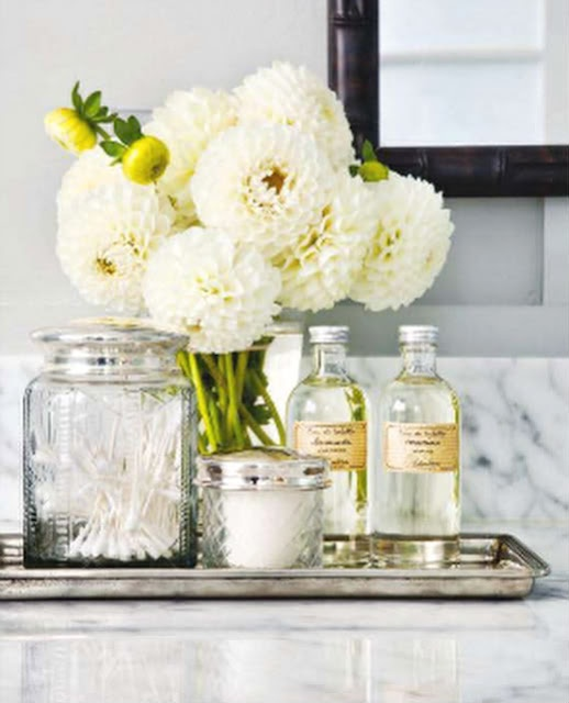 Bathroom styling using the following 3 elements. 1) white and green flowers 2) glass jars with silver lids 3) Silver tray