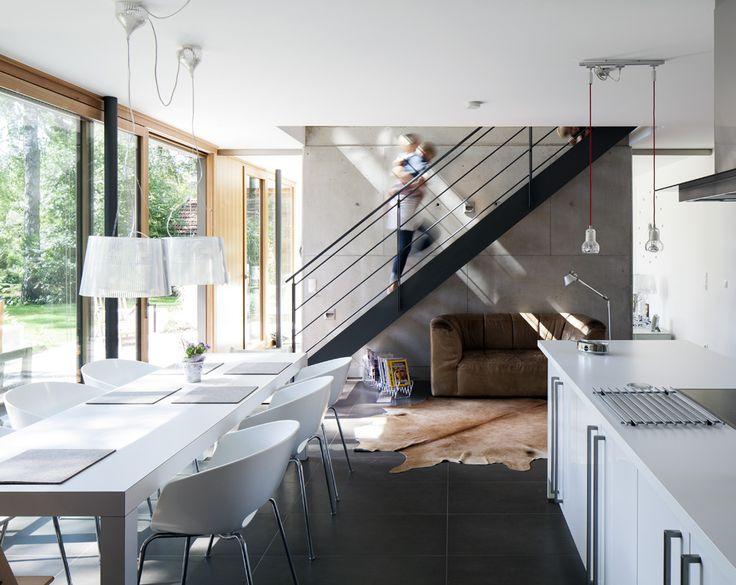 Hinter Treppe und Wand liegt der Wohnbereich verborgen. Die Fliesen speichern die Wärme der Fußbodenheizung.
