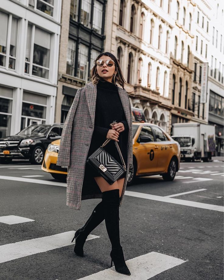 Pam Hetlinger of the fashion, beauty, lifestyle, and travel blog, The Girl From Panama, styles a black sweater dress with over the knee stiletto boots and a plaid trench coat
