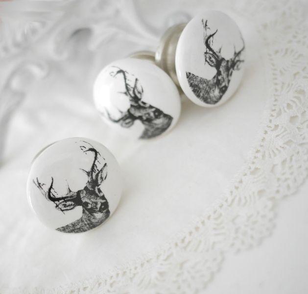 Vit porslins knopp med motiv i svart av en hjort / ren med horn. Med silverfärgad metall stomme samt krage. I greppvänlig modell