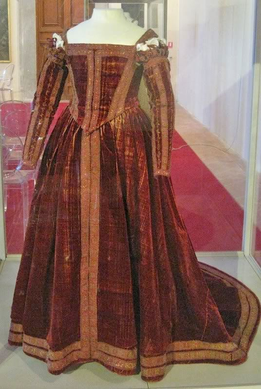 "ca. 1560 Italy, Florence. Red Dress of Pisa. Currently in the Museo di Palazzo Reale, Pisa. Believed to be from 1560, this is called the ""Red Dress of Pisa."" It is a Florentine gown from the sixteenth century - it was found on a wooden effigy at San Matteo. It is housed at the Palazzo Reale di Pisa (Museum Nazionale). It is made of red velvet with gold couched trim."