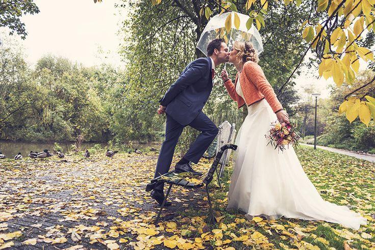 Wedding couple kissing in the rain - autumn