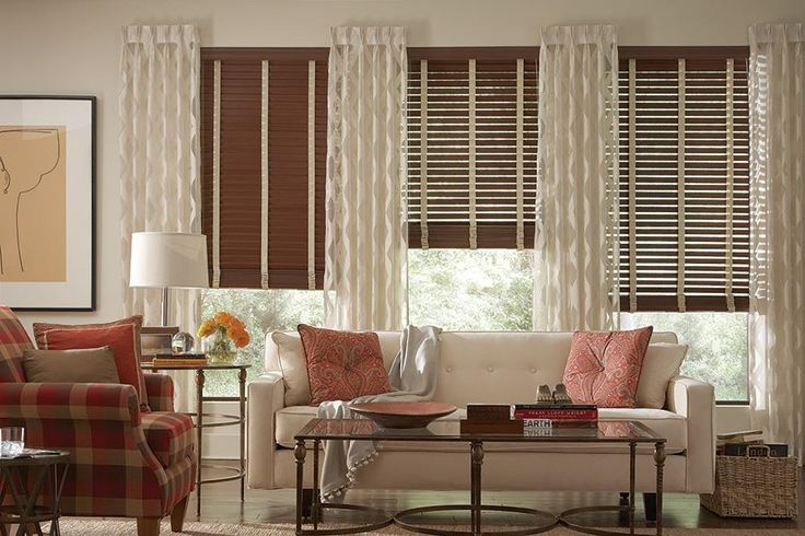 Faux dark wood blinds with cloth tape by Lafayette Interior Fashions - Fidelis wood blinds. This living room design has combined dark wood blinds with pleated drapery sheers for a stunning look. The drapery sheers make the windows look larger and they become a focal point. These are panels, not pull drapes - they are stationary. If you do want more room darkening options you could have the curtain rod go all the way across the wood window.   Find more living room ideas on our site.