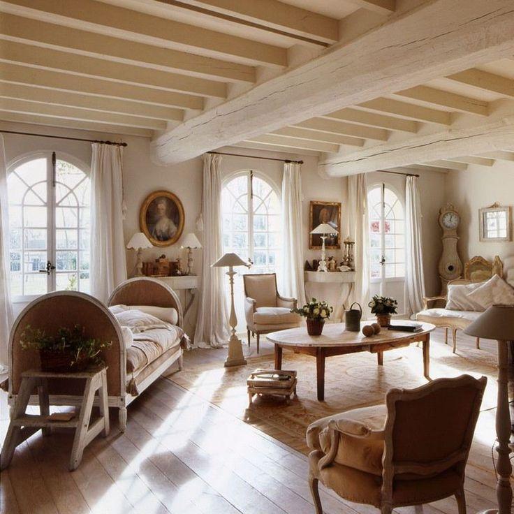 décoration maison de campagne blanche - salon blanc aux poutres exposées, aménagé avec un canapé rustique en bois, des fauteuils en blanc et une table basse ronde