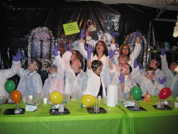 Mad Scientist in training with the Mad Scientist and her team. My son's birthday party I did in my science lab (garage). My son has a real kids science lab coat on and the others have disposable ones from http://www.mrdisposable.com/product/LC The goggles are from Dollar Tree and found the purple gloves at Big Lots. Cheap box of them. Was a great party.