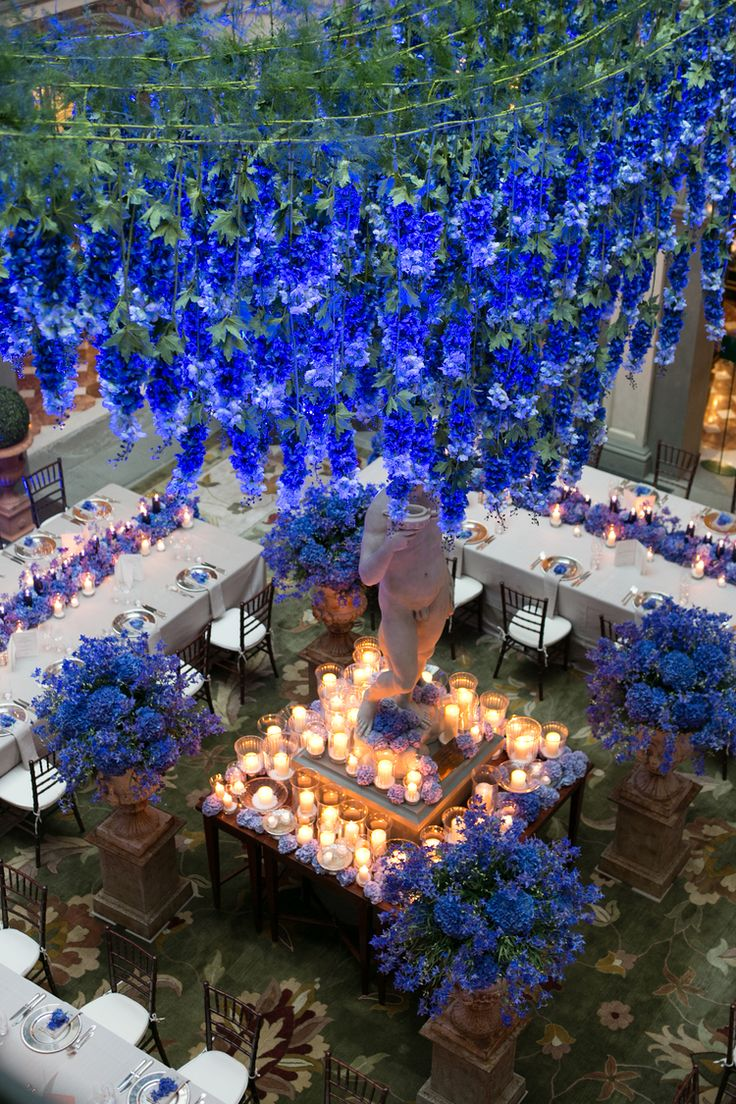 Blue wedding dinner set up, scenographic blue delphinium hanging from the ceiling