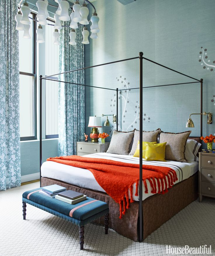 In a Greenwich Village bedroom, the walls are covered with stenciled abstract trees, and a brown bedskirt softens the steel four-post bed. The Red Tape bench from Bunny Williams Home is upholstered in Holly Hunt's Take Direction with trim by Passementerie.  ERIC PIASECKI