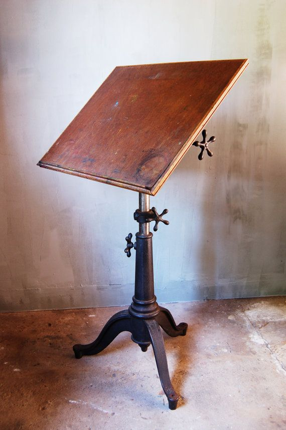 Early 20th century art table with cast iron Queen Anne style base. Wood top with fully adjustable faucet style handles, used to adjust the height