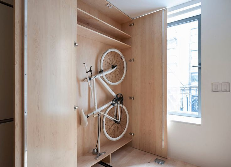 Hill's ThinBike, features folding handlebars and pedals that allow it to easily fit snugly against a wall (or in this custom-sized cabinet).