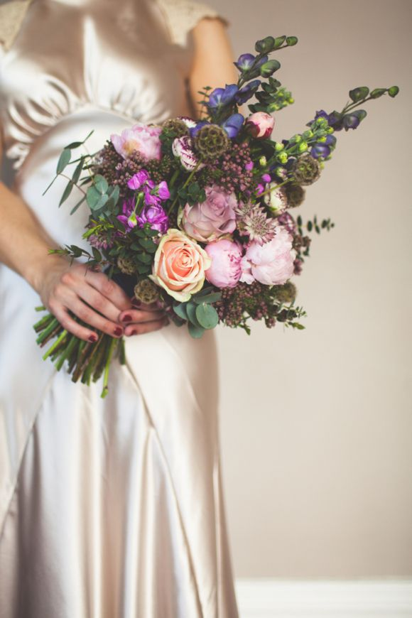 Gorgeous wedding bouquet in peach, pink and purple tones.