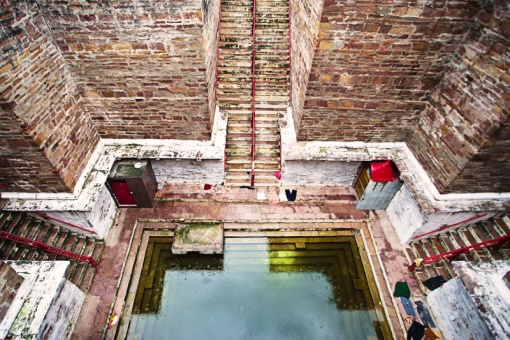 lolarka kund, step well India. Women and men enter down different stairways, women leave their saris on the steps as they leave. Water levels rise and fall
