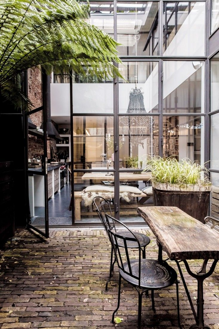 factory windows amsterdam garden maurius haverkamp ; Gardenista. In Amsterdam, designer Maurius Haverkamp's home in a former warehouse is designed around a patio with walls of glass and steel that send sunlight into all areas of the house. Photograph via Kikette Interiors.