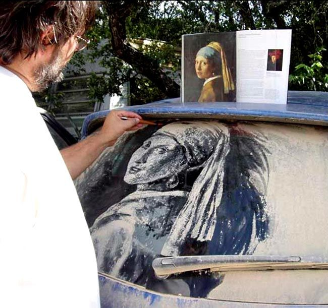 """Dirty car art, in Austin TX. This guy wanders around parking lots and finds the dirtiest rear windshields he can, then """"paints"""" art into them by selectively removing some of the dirt."""