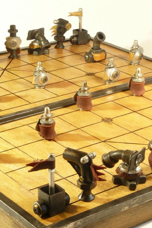 Xiang Qi (Ca tuong): Chinese chess set - The figurines are made from different parts in steel, aluminium, brass, leather out-take, glass marbles… I used an old motor copper wire to sew the leather. The game board is also a storage case : wood burned with patina, steel reinforcements. Unique piece. 30′ x 27′. The Emperor height: 5′.