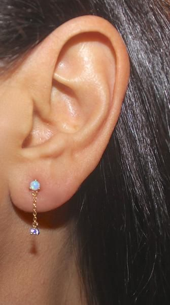 Opal ear piercing gold chains earring These dainty opal and gold chain earrings feature a tiny round fire opal stone on the stud and a bezel zircon stone that dangles at the end of the ear chain. This pair of opal earrings with gold chain are versatile for everyday and look awesome paired with other opal ear piercing jewelry cartilage opal