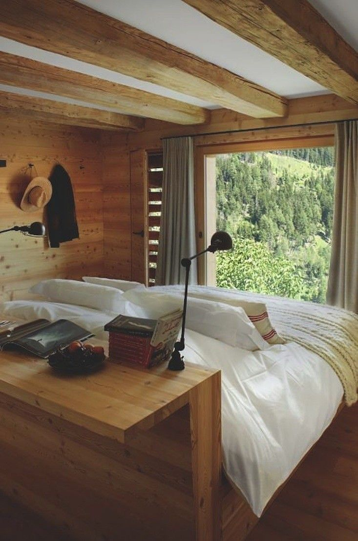 The guest rooms of Montagne Alternative in Switzerland have beds with a headboard/console table in the middle of the room facing a view of the Alpsgood