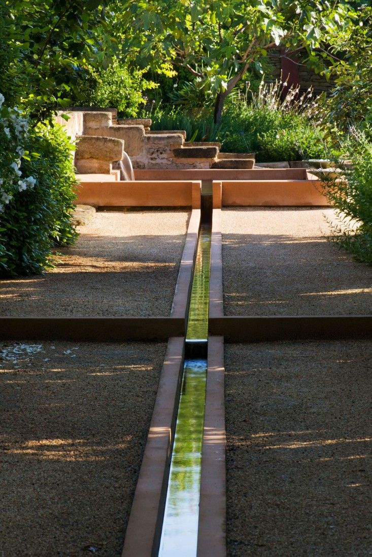 A manmade stream at La Noria flows from the stone fountain and down the Allée des Cypres, a shady, cypress-lined enclosure in the Water Garden.