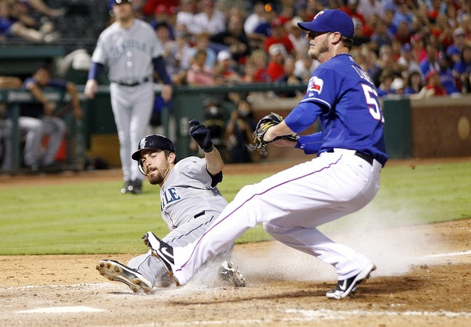 ARLINGTON, TX - MAY 29: Dustin Ackley #13 of the Seattle Mariners score on a wild pitch by Mark Lowe #57 of the Texas Rangers at Rangers Ballpark in Arlington on May 29, 2012 in Arlington, Texas. (Photo by Rick Yeatts/Getty Images)